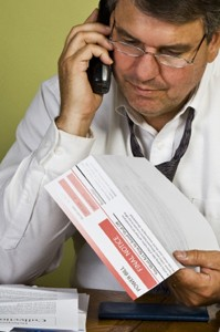 Photo Of A Man On The Telephone Holding A Bill